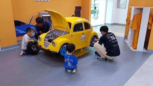 모형 자동차를 정비 중인 아이들과 아빠들.