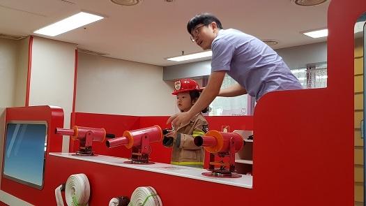 한 아이가 소방관복을 입고 화재를 진압하는 체험을 하고 있다.