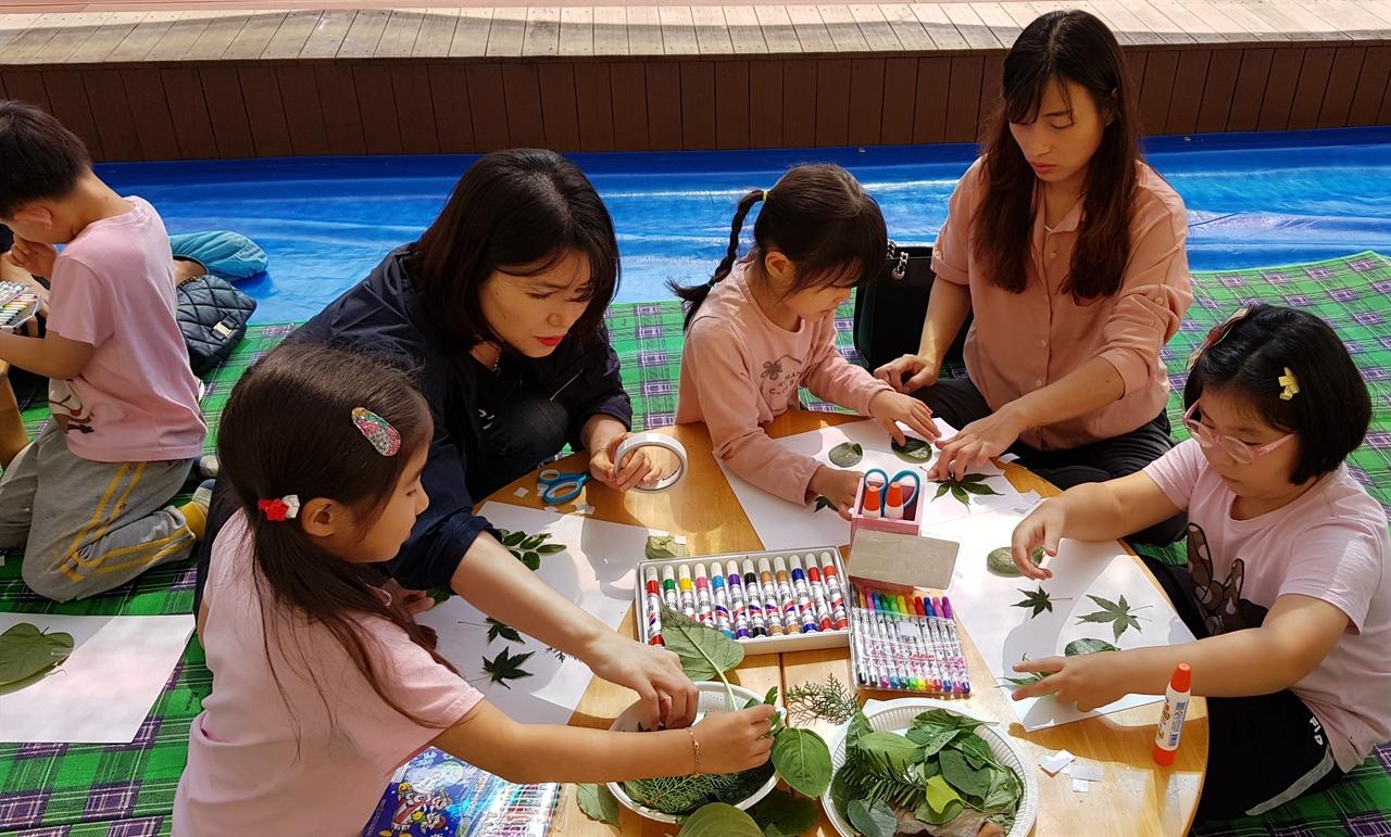천안성정유치원 옥상 정원에서 유아와 학부모가 함께 나뭇잎 콜라주 체험 수업을 하고 있다.