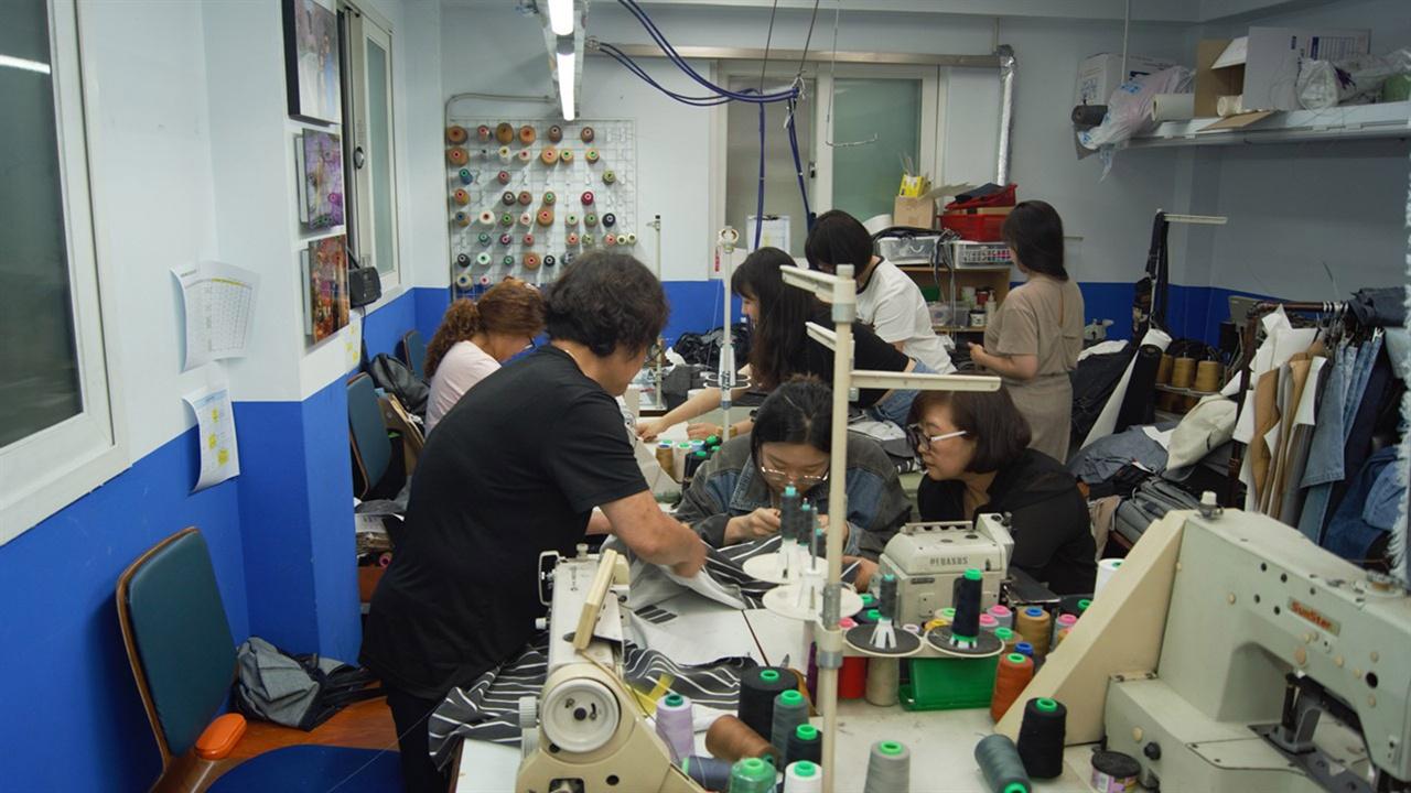 패션디자이너를 꿈꾸는 청년들이 창신·숭인 지역 봉제장인들과 의상을 제작하고 있는 모습. KT&G는 전국 디자인공모전을 통해 최종 12개 팀을 선발했으며, 선발된 디자인 팀은 '20대의 희노애락'을 주제로 봉제장인들과 협업으로 의상을 제작했다.