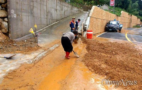 태풍 '미탁'으로 폭우가 내리면서 창원의 한 도로에 토사가 유출되어 복구작업이 진행되고 있다.