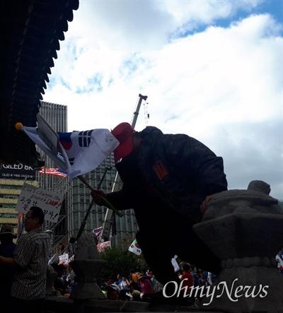 한 보수정당 및 단체 집회 참가자가 출입 제한 구역인 사적 171호 고종 어극 40년 칭경 기념비전으로 들어가며 동물 석상을 짚고 있다.