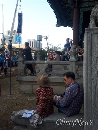 3일 자유한국당과 범국민투쟁본부가 이끈 문재인정권 규탄 집회에서 일부 참가자들이 출입 제한 구역인 사적 171호 고종 어극 40년 칭경 기념비에 들어간 모습. 만세전 계단에 앉아 빵을 나눠먹고 있는 모습이다.