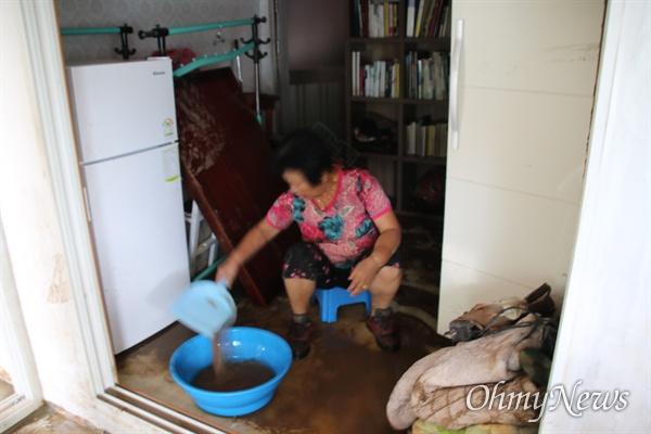 제18호 태풍 '미탁'이 지나간 후 피해를 입은 경북 영덕군 강구면에서 한 주민이 안방에서 물을 퍼내고 있다.