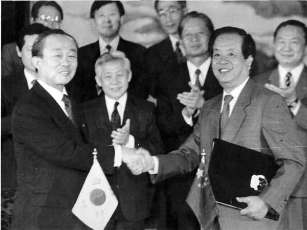 지난 1992년 8월24일 베이징 댜오위타이(釣魚臺) 국빈관에서 이상옥 외무장관과 첸치천(錢其琛) 중국 외교부장이 `한중 외교관계 수립에 관한 공동성명'에 서명하고 악수하는 모습.