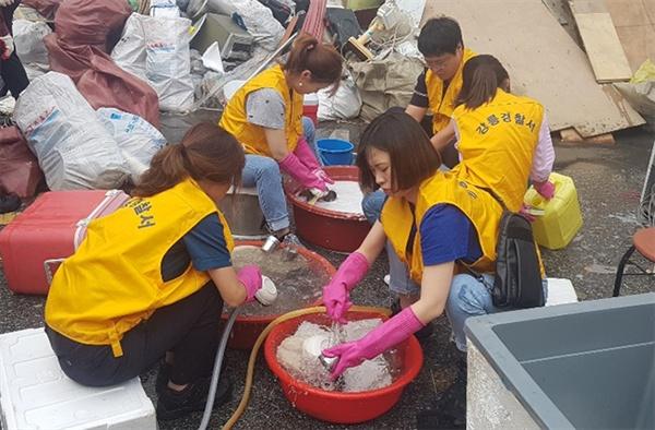4일 강릉경찰서 직원들이 침수된 경포호수 인근 진안상가에서 수해복구 활동을 벌이고 있다.
