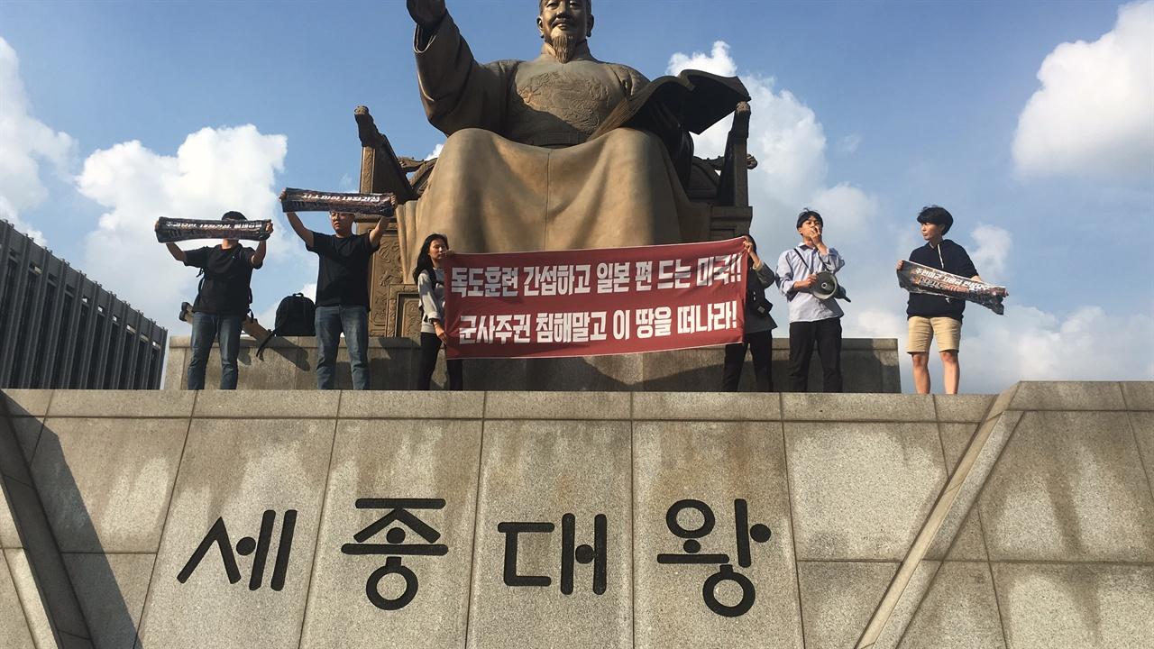 한국대학생진보연합 소속 대학생들이 세종대왕 상 위로 올라가 시위를 진행하고 있다