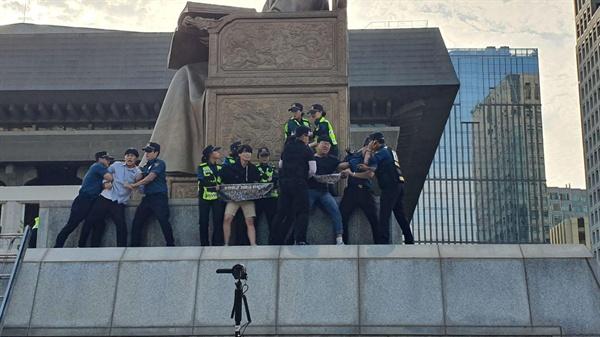 세종대왕 상에 올라간 대학생들이 경찰들에 의해 강제 연행이 되고 있다.
