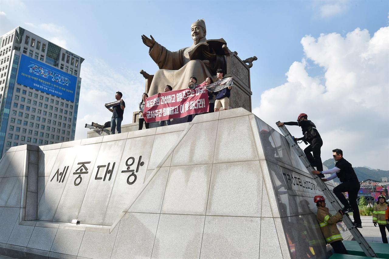 한국대학생진보연합 소속 대학생 6명이 4일 오후 서울 세종로 광화문광장내 세종대왕 동상에 올라가 '한일 군사정보보호협정(GSOMIA·지소미아)' 파기를 방해하는 미국을 규탄하는 기습시위를 벌이고 있는 가운데 경찰이 학생들을 해산 시키기 위해 사다리를 이용해 동상위로 올라가고 있다.2019.10.04