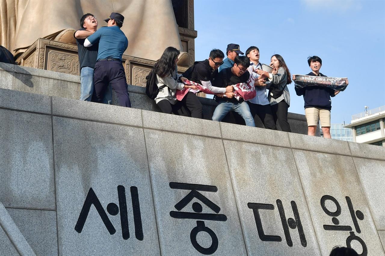 한국대학생진보연합 소속 대학생 6명이 4일 오후 서울 세종로 광화문광장내 세종대왕 동상에 올라가 '한일 군사정보보호협정(GSOMIA·지소미아)' 파기를 방해하는 미국을 규탄하는 기습시위를 벌이자 경찰이 이들을 해산시키기 위해 몸싸움을 벌이고 있다. 2019.10.04