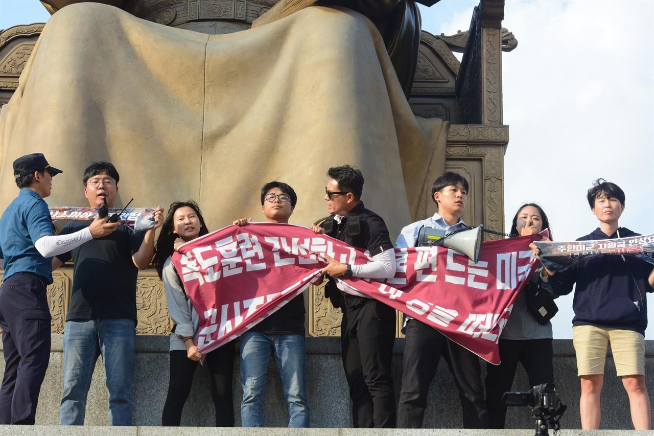 한국대학생진보연합 소속 대학생 6명이 4일 오후 서울 세종로 광화문광장내 세종대왕 동상에 올라가 '한일 군사정보보호협정(GSOMIA·지소미아)' 파기를 방해하는 미국을 규탄하는 기습시위를 벌고 있는 가운데 경찰에 시위학생들이 펼쳐든 현수막을 강제로 빼앗고 있다. 2019.10.04