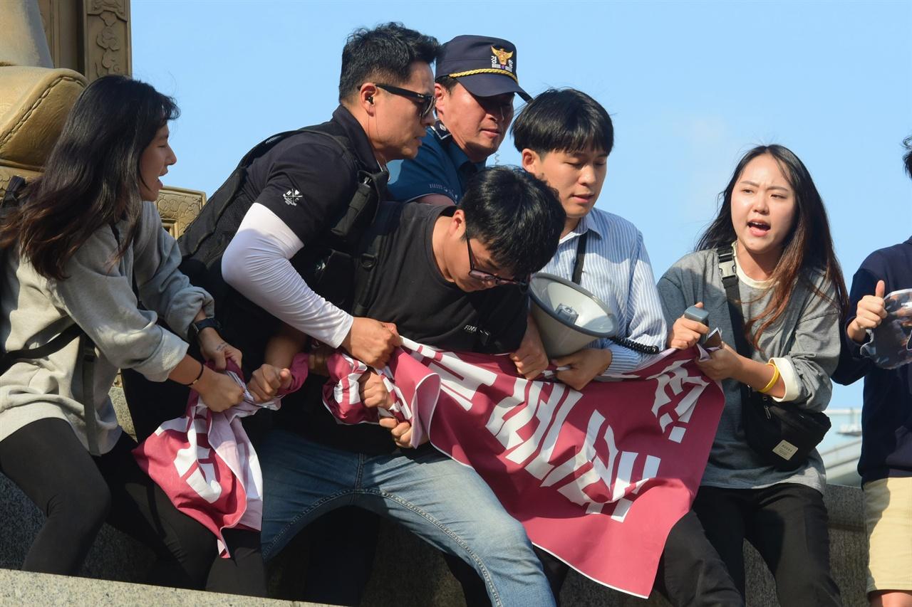 한국대학생진보연합 소속 대학생 6명이 4일 오후 서울 세종로 광화문광장내 세종대왕 동상에 올라가 '한일 군사정보보호협정(GSOMIA·지소미아)' 파기를 방해하는 미국을 규탄하는 기습시위를 벌이자 경찰이 학생들이 펼쳐든 현수막을 강제로 빼앗고 있다. 2019.10.04