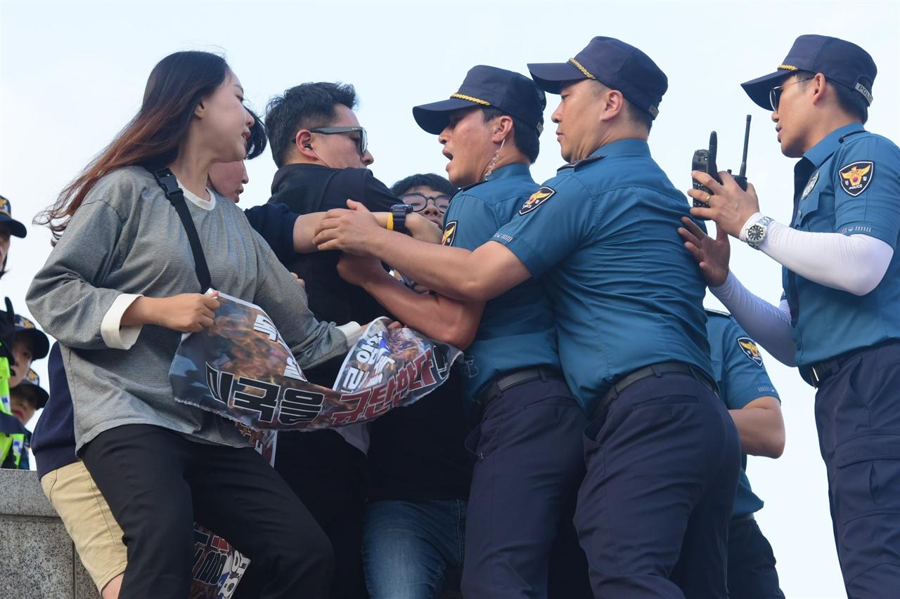 한국대학생진보연합 소속 대학생 6명이 4일 오후 서울 세종로 광화문광장내 세종대왕 동상에 올라가 '한일 군사정보보호협정(GSOMIA·지소미아)' 파기를 방해하는 미국을 규탄하는 기습시위를 벌이자 경찰이 학생들이 펼쳐든 현수막을 강제로 빼앗기 위해 몸싸움을 벌이고 있다. 2019.10.04