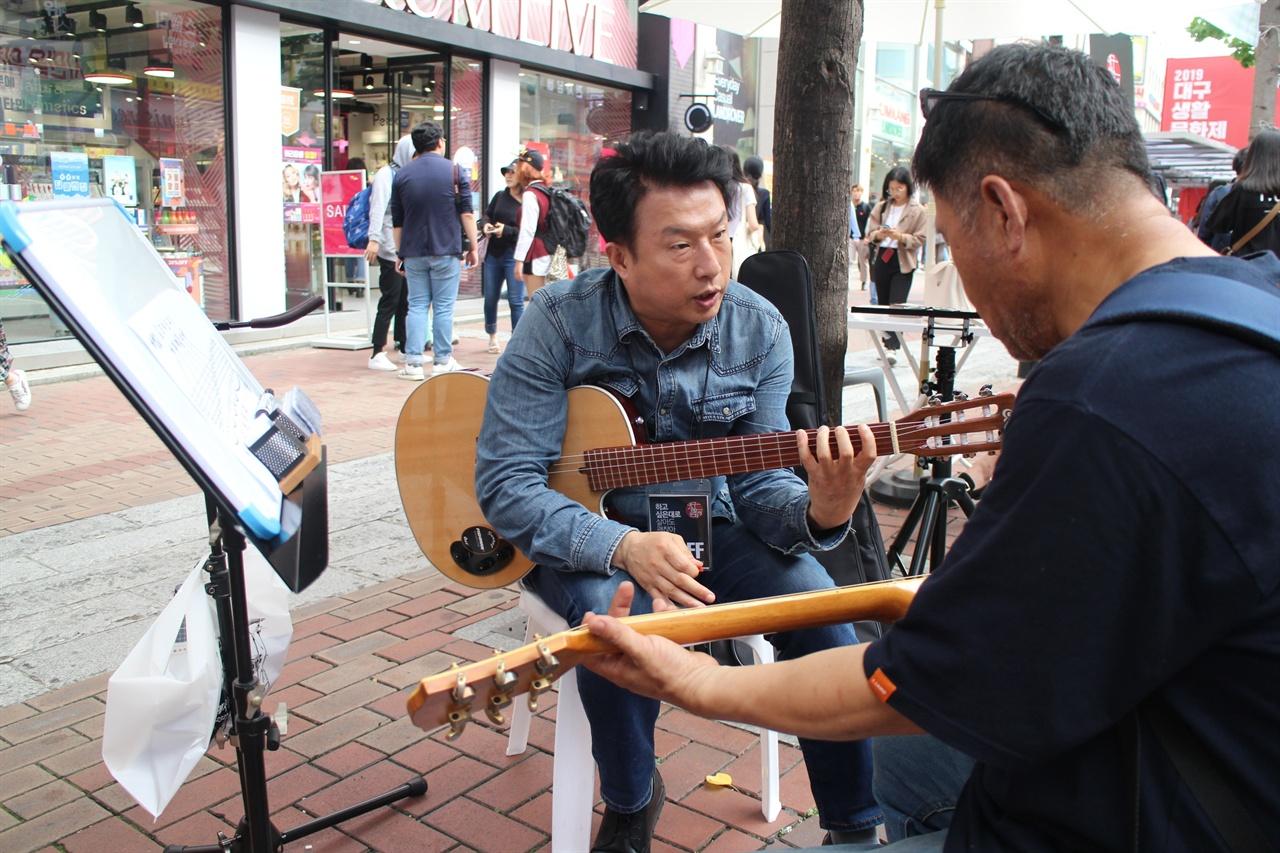 기타를 가르쳐주고 있는 모습 아마추어 기타동호회 회원이 직접 일반 시민에게 기타를 가르쳐주고 있는 모습이다.
