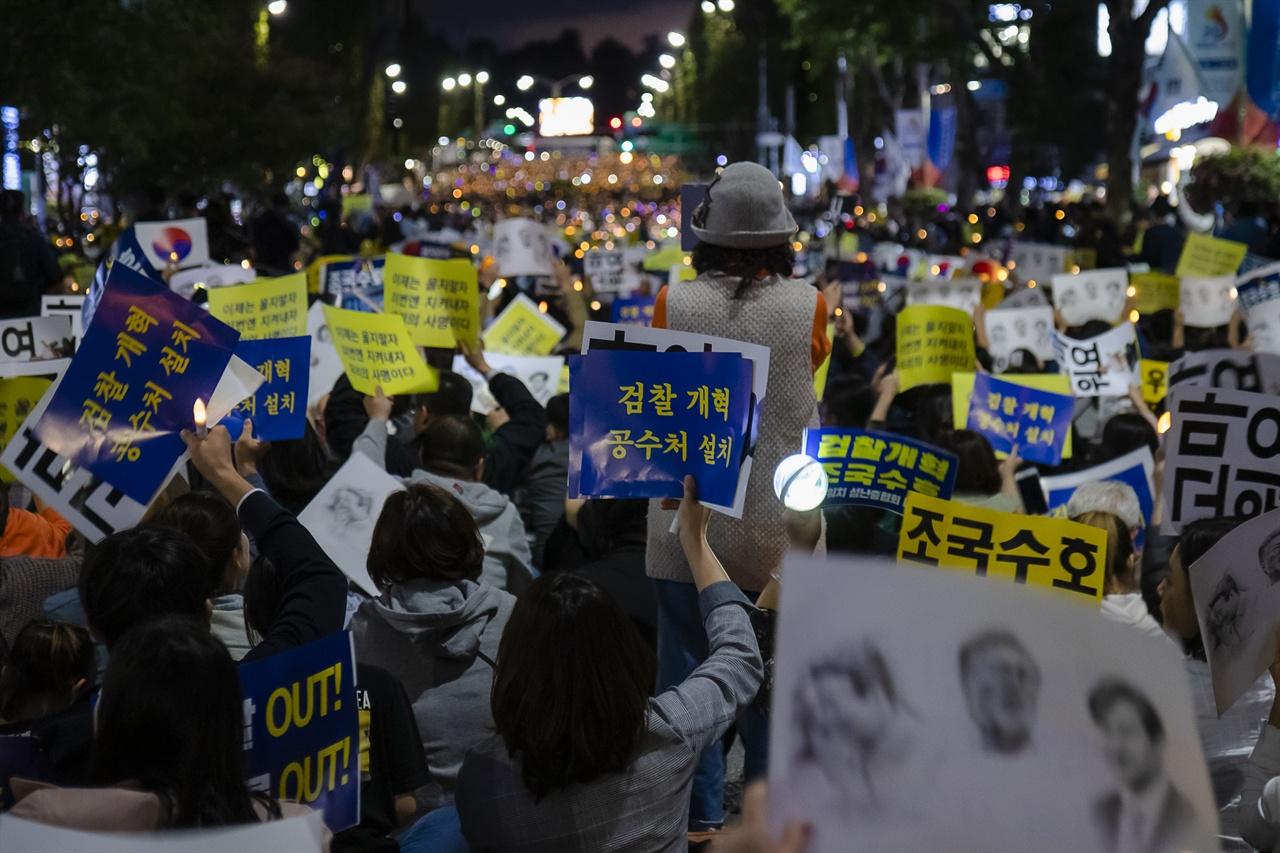 '제8차 사법적폐청산을 위한 검찰개혁 촛불문화제' 에 참석한 시민들이 보이지 않는 무대를  보며 피켓을 들고 구호를 외치고 있다.
