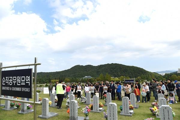 세월호 참사로 순직한 교사들이 묻혀있는 '순직공무원묘역'에서 참가자들이 이야기를 듣고 있다.