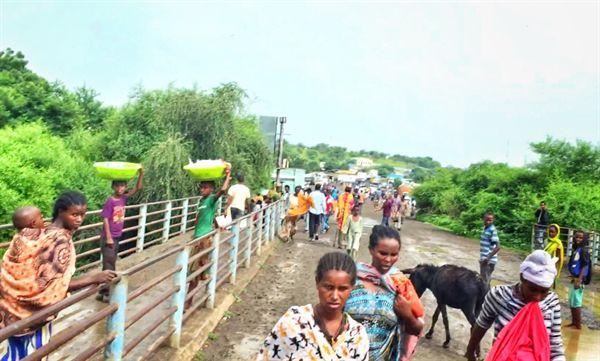 수단 남부 갈라밧 마을과 에티오피아 북부 메테마 마을을 잇는 국경의 다리를 건너는 사람들