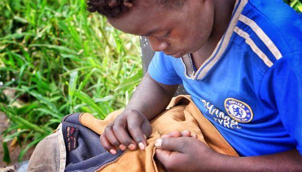 에티오피아 수도 아디스아바바의 소년. 옷의 솔기를 따라 빈대를 잡고 있다. '아디스 아바바 Addis Ababa' 는 암하라어로 '새로운 꽃' 을 의미한다