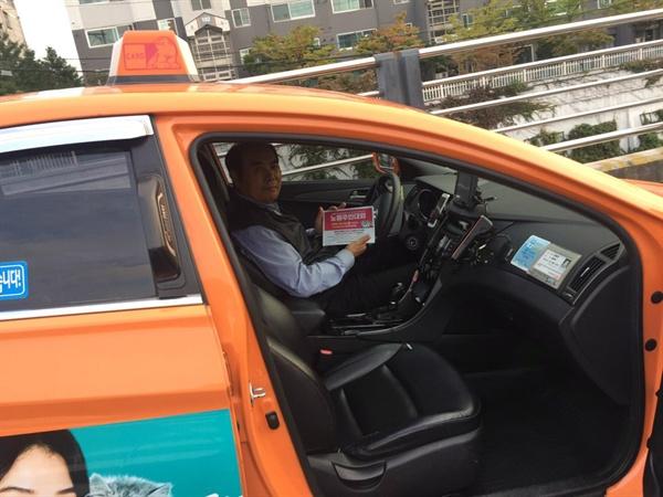 주민대회 홍보 전단을 들고 웃는 택시노조 조합원.