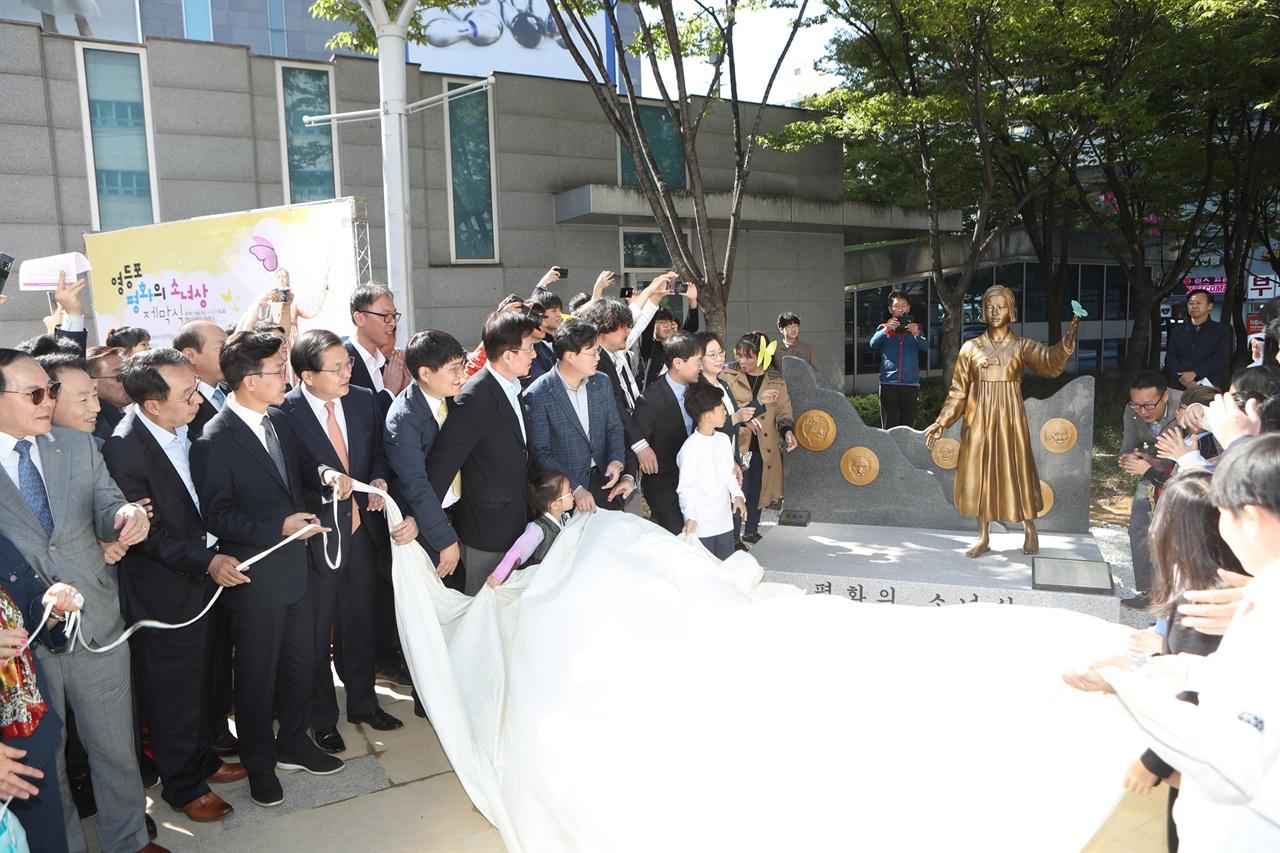 9일 서울 영등포구 타임스퀘어 광장에서 열린 '평화의 소녀상'이 제막식에서 참석자들이 소녀상을 공개하고 있다.