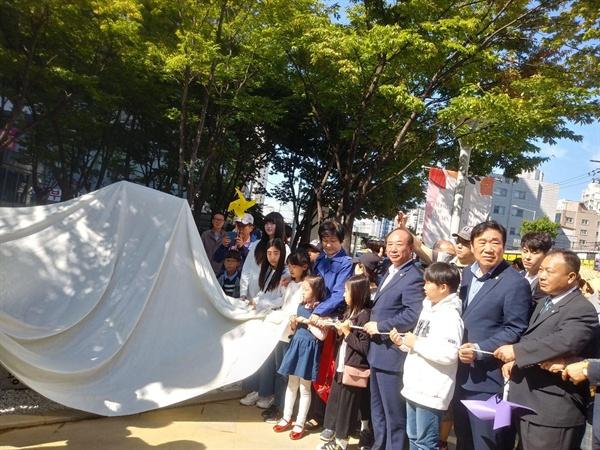 소녀상 제막식  어린이 청소년이 함께 제막식 천을 열고 잇다.