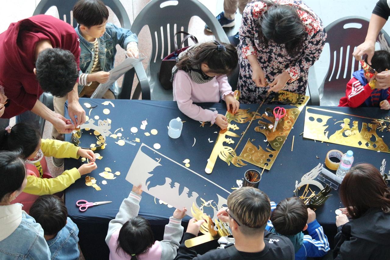 가족 단위 방문객들이 어린 아동과 함께 신라왕관을 만들고 있다. 신라 왕관을 만들고 있는 관광객들의 모습이다.