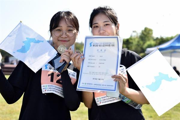 제12회 대전통일마라톤대회가 10월12일 오전 엑스포다리아래 한밭수목원 천변일대에서 개최되었다.  기록증과 완주메달을 받은 참가자들이 환하게 웃고 있다. [사진-대회준비위 제공]