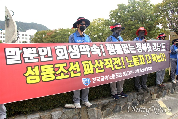 전국금속노동조합 경남지부 성동조선지회 조합원들이 경남도청 정문 앞에서 펼침막을 들고 서 있다.