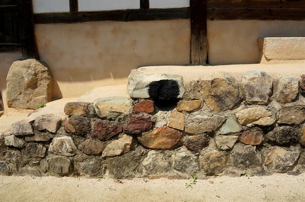 양진당 굴뚝 기단에 구멍을 내서 만든 원시굴뚝이다. 순박하게 미소 짓고 있다.