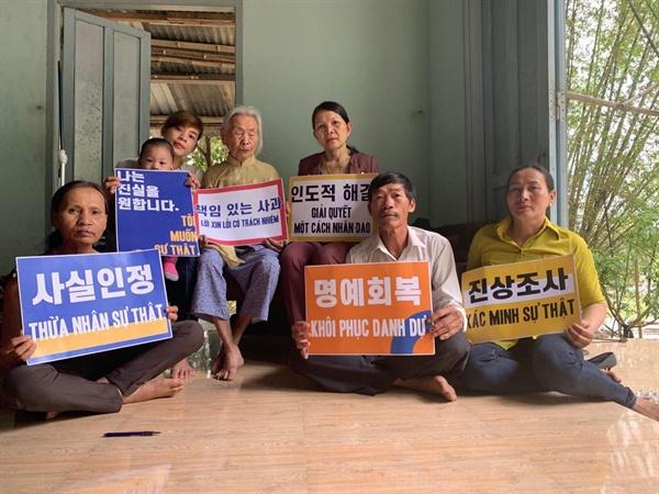 반꾸엇 마을 학살 피해자 쯔엉티쑤엔과 가족들 한국정부의 진상조사, 사실인정, 피해자에 대한 명예회복 등을 요구하며 피켓을 들었다.
