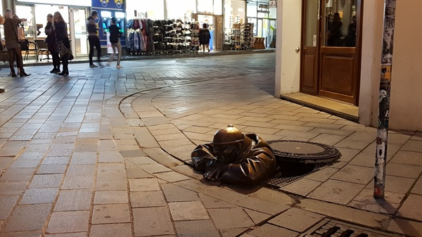 맨 앳 워크 동상 맨홀 뚜껑을 열고 나온 그는 지나가는 사람들을 훔쳐본다.