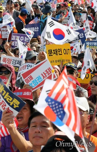 '문재인 아웃' 한국당 집회에 등장한 피켓 자유한국당 주최로 19일 오후 서울 광화문 세종문화회관 앞에서 열린 '국민의 명령, 국정대전환 촉구 국민보고대회'에서 참가자들이 문재인 대통령 퇴진을 요구하는 피켓을 들고 있다.