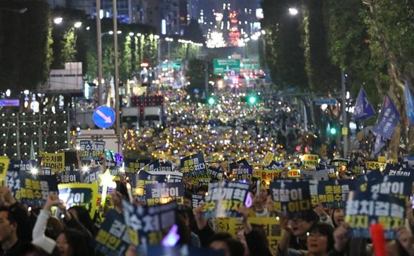 19일 오후 서울 서초구 서울중앙지법 인근 서초대로에서 열린 검찰 규탄 촛불집회에서 참가자들이 손팻말을 들고 구호를 외치고 있다.