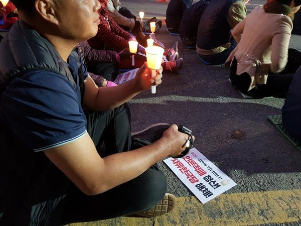촛불을 든 광주 시민 한 광주시민이 한 손에 촛불을 든 채 구호를 외치고 있다.