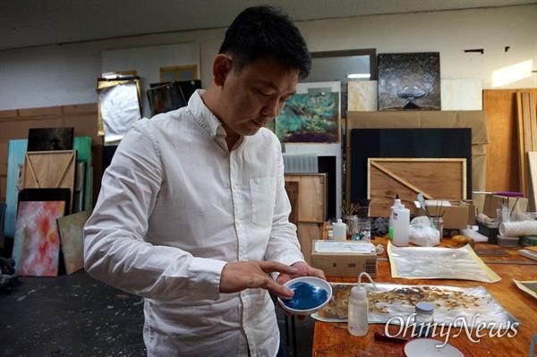 김선태 작가가 석채로 색을 만드는 과정을 직접 보여줬다. 석채 한 스푼을 그릇에 덜어낸 뒤 아교와 물을 적당히 섞은 뒤 손으로 문질렀다.
