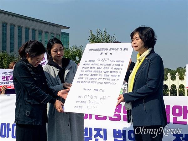 시민단체 정치하는엄마들과 하준·태호·유찬·민식이 부모들이 21일 오전 서울 여의도 국회의사당 정문 앞에서 어린이생명안전법안 통과를 촉구하는 기자회견을 진행하고 있다. 이정미 정의당 의원이 정기국회 내 법안통과 동의서에 서명한 뒤 태호·유찬이 부모들에게 전달하고 있다
