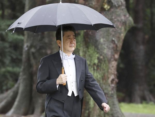 아베 신조(安倍晋三) 일본 총리가 22일 오전 나루히토(德仁) 일왕의 즉위식이 열리는 도쿄 왕궁 규추산덴(宮中三殿) 중 가시코도코로(賢所)로 우산을 받쳐 들고 걸어가고 있다.