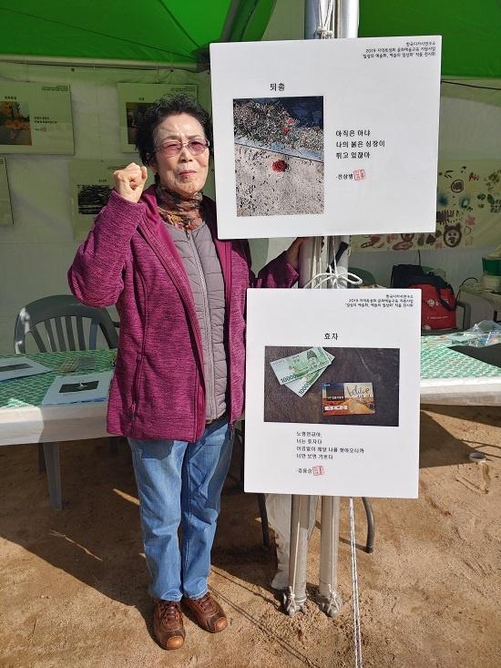 전삼병 할머니가 자신의 디카시 <퇴출> 전시 액자(위쪽) 앞에서 포즈를 취하고 있다.