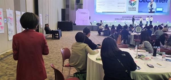 23일 한-OECD 국제교육컨퍼런스의 원탁토론회에서 한 참석자(서 있는 이)가 서명지를 받기 위해 걸어가고 있다.