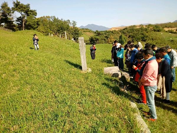 역사진흥원 주최 역사 탐방 참가자들이 홍의장군 묘소를 참배하고 있다.