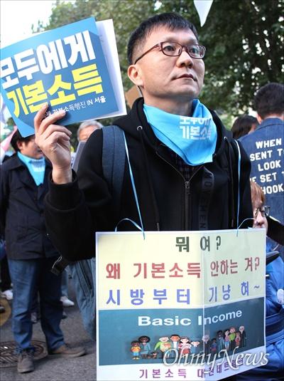 """26일 전 세계 10개국 26개 도시에서 기본소득 지지자들이 기본소득을 알리고 기본소득 실현을 요구하는 """"국제기본소득행진(Basic Income March)""""을 동시에 진행했다. 서울에서도 대학로에서 보신각까지 150여 명의 지지자들이 행진을 벌이며 시민들에게 기본소득의 필요성을 설명했다. 사진은 기본소득대전네트워크 회원인 이선배(51.독서지도사)씨의 행진 모습."""