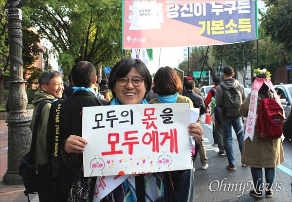 """26일 전 세계 10개국 26개 도시에서 기본소득 지지자들이 기본소득을 알리고 기본소득 실현을 요구하는 """"국제기본소득행진(Basic Income March)""""을 동시에 진행했다. 서울에서도 대학로에서 보신각까지 150여 명의 지지자들이 행진을 벌이며 시민들에게 기본소득의 필요성을 설명했다. 행진에 참여한 한승인(55)씨가 """"모두의 몫을, 모두에게""""라고 적힌 손 피켓을 들고 있다."""