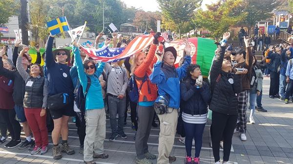 10월 26일 오전 '서울둘레길, 세계인이 걷는다' 페스티벌 참가자들이 우이동 '만남의광장'에서 출발하기에 앞서 각국의 깃발을 흔들고 있다.