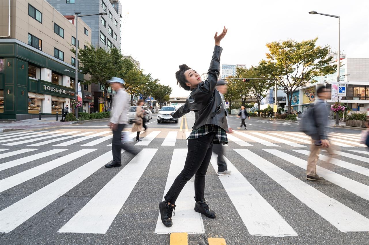 인터뷰를 마치고 연습실 밖으로 나와 거리에서 그가 추고 있는 춤의 포즈를 취하고 있다.
