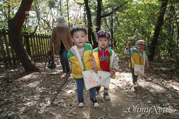 예쁜아이어린이집 아이들이 25일 오전 서울 동작구 와우산에서 나뭇가지를 지팡이 삼아 산책로를 걷고 있다.