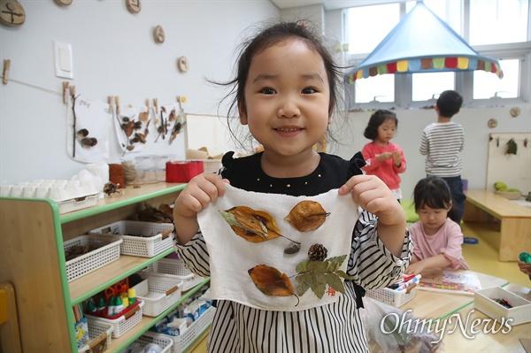 25일 오후 서울 영등포구 다온어린이집에서 한 아이가 생태친화 수업으로 가져온 나뭇잎과 솔방울로 꾸민 작품을 자랑하고 있다.