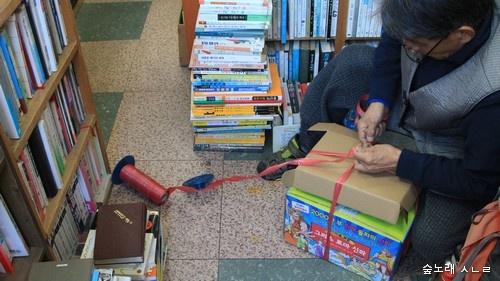 고른 책을 상자로 둘 묶는다.