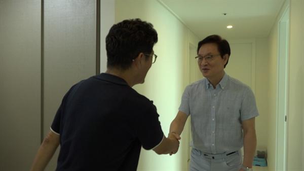 정두언 전 의원이 김병기 감독과 악수를 하고 있다.
