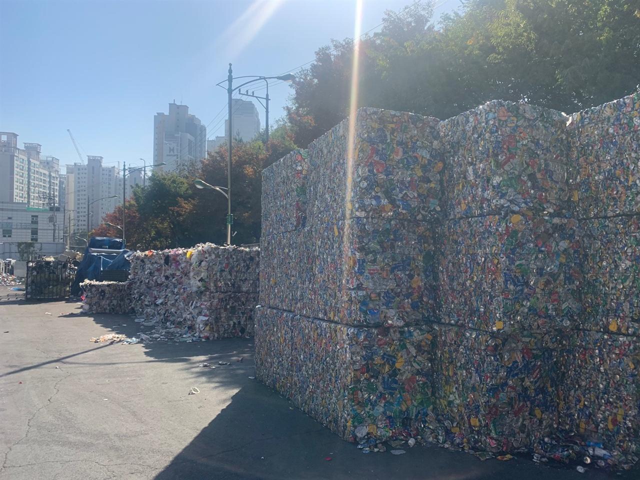 강북 재활용품 선별처리 시설 입구 주변에 쓰레기가 분류되어 묶여 있는 모습을 볼 수 있다.