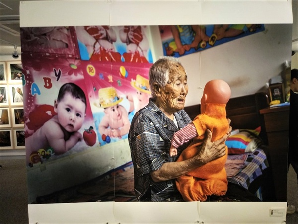 아기 인형을 안고있는 고 이수단 할머니 홍보 팜플릿에 담긴 이수단 할머니는 위안부 강제 동원으로 인해 성병에 걸려 아이를 가질 수 없게 되었다. 그래서 아이에 대한 집착이 커져 아이 인형을 자식처럼 여기며 끌어 안았다.